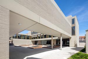 Während sich Aula und Schulräume zum Innenhof großflächig öffnen, ist die<br />Fassade zur Stadt eher introvertiert und geschlossen gestaltet. Helle, schmale<br />Klinker, gefasst von horizontalen Betonfertigteilen, geben der Gebäudehülle<br />eine feine Struktur, die zeitgemäß und in handwerklicher Präzision gefertigt<br />ist.<br />