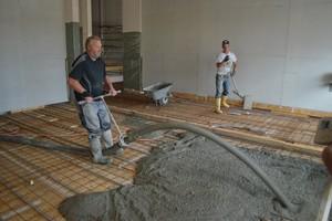Einbringen von Ortbeton auf eine Balkendecke mit OSB als verlorene Schalung. Oft wird der Holzbau bis Dachkonstruktion fertiggestellt und der Beton am Schluss eingepumpt