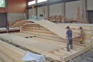 Bei der Holzrahmenbauweise werden die Rohmaterialien in die Zimmerei geliefert, dort abgebunden, zu Elementen vorgefertigt und dann auf die Baustelle transportiert<br />