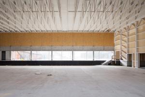 Über den Stahlbetonträgern an der Südseite sind die OSB-Platten angebracht, die mit Textil bespannt, die Akustik in der Halle verbessern