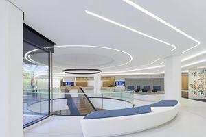 Der Raum wird durch eine zentrale Treppe dominiert, welche in den Bestand integriert wurde. Die Freitreppe aus Eiche und schwarzen Wangen bildet einen starken Kontrast zur weißen Grundstimmung und verbindet Basisgeschoss und Foyer miteinander.<br />