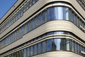 Die hellen, unterschiedlich großen Keramikplatten sind im wilden Verband verlegt und beleben das Fassadenbild durch ihre wahlweise fein horizontal gerillte Linienstruktur oder glatte Oberfläche.<br />