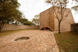 Für die Außenwände der Kapelle wurden die alten Ziegel des Hauses, das voher dort stand, verwendet. Ihre Patina sorgt dafür, dass sich die Anlage, das Gebäude und die Natzur zu einer Einheit verbinden.
