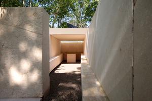 Souto de Mouras Kapelle bildet einen langgestreckten Hof, der beidseitig von Sitzbänken gefasst ist. Der kleine Altar mit Taufbecken auf der Rückseite ist mit einer Steinplatte überdacht