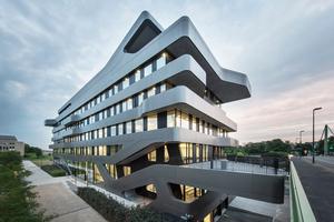 Der Baukörper verbindet die verschiedenen Verkehrsebenen miteinander. Dank seiner Farbgebung in einem tiefen, metallisch schimmernden Grauton und seiner skulpturalen Dynamik integriert er sich harmonisch in den Straßenraum