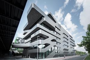 Der Baukörper verbindet die verschiedenen Verkehrsebenen miteinander. Dank seiner Farbgebung in einem tiefen, metallisch schimmernden Grauton und seiner skulpturalen Dynamik integriert sich die FOM harmonisch in den Straßenraum.