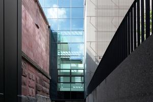 Links der Jugendstilbau mit Athene-Trakt, über den der Neubau mit dem Bestand verbunden ist. Die Verglasung umschließt den Zugang zum Altbau und bringt eine Menge Tageslicht ins zentrale Atrium
