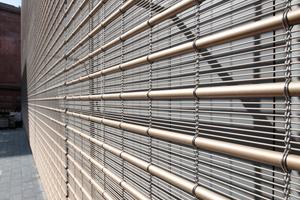 Drahtstäbe und schlanke Rohre sind zu einem transparenten Teppich verwoben. Vor Fernstern und anderen Öffnungen fehlen die Rohre, die Transparenz wird erhöht