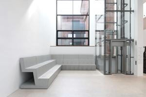 Auf der anderen Seite des Zugangs der verglaste Lift und wieder Sitzmöbel für den Flaneur