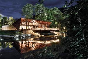 Bei Dunkelheit spiegeln sich die Lichter durch die Glasfassade stimmungsvoll auf der Wasserfläche<br />