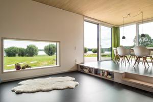 Die Anordnung der Innenräume und die Fensteraufteilung wurden so gewählt, dass die Blicke auf den See bestmöglich inszeniert werden. So sitzt das Fenster im abgesenkten Wohnraum bewusst tief, um den Garten und den See auch im Sitzen wahrzunehmen. Die Sichtholzoberflächen der Decken stellen einen reizvollen Kontrast zum dunklen Boden her.<br />