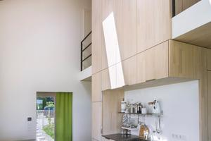 """Eine zweigeschossige """"Holz-Box"""" beinhaltet im Erdgeschoss die Sanitärräume und alle technischen Einrichtungen. Sie ist von einer offenen Galerie im Obergeschoss umgeben und wirkt wie ein eingestellter Solitär, um den herum Diele, Kochen, Essen und Wohnen als großzügiger Flächenverbund angeordnet sind"""