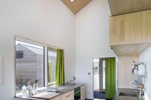 Die akustisch wirksamen Dach- und Deckenuntersichten im Klimaholzhaus schaffen auch bei modern sparsamer Möblierung und dem zurückhaltenden Einsatz von Heimtextilien beste Akustik im Haus