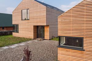Fenstereinschnitte über Eck betonen den monolithischen Charakter der Gebäudekubaturen ohne Dachüberstände oder andere hervortretende Gestaltungselemente.<br />