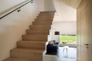Eine einläufige Treppe führt ins Obergeschoss auf die Galerie. Die Akustik-Oberflächen der Decken- und Dachelemente haben einen sehr positiven Einfluss auf die Hörsamkeit in der offen gestalteten Raumanordnung im Haus<br />