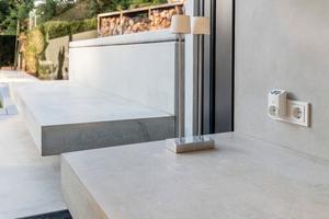 Betonsitzbänke im Innenbereich setzen sich auf der Terrasse fort. So werden die beiden Bereiche optisch miteinander verbunden