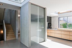Die Fertigteil-Betonelemente werden auch kreativ für die Innenausstattung eingesetzt. Hier ein Betonschrank mit Schiebetür aus Milchglas als Garderobe