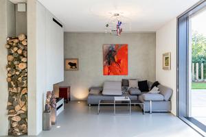 Raumteiler in Sichtbeton-Optik zwischen Küche und Essbereich. Der Kamin und eine Nische mit Feuerholz sind wirkungsvoll integriert