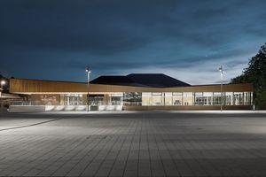 Das nahezu vollverglaste Erdgeschoss lässt die Innenräume nachts nach außen hin sichtbar werden