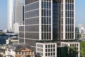 Das Gebäude nimmt bewusst die Kommunikation mit der Stadt auf: Mit einer Bekleidung aus hellem Trosselfels und zurückspringenden bronzeeloxierten Fensterprofilen fügt sich das Ensemble perfekt in die charakteristische Skyline Frankfurts ein