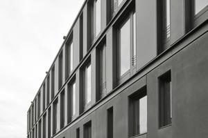 Während die Fassade in den unteren Ebenen aus schwarz durchgefärbtem Sichtbeton besteht, kommt in den oberen Ebenen schwarz eloxiertes Aluminium zum Einsatz