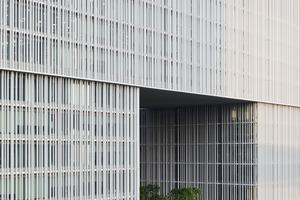 Im 4., 10. und 16. Geschoss springt die Fassade jeweils um 45cm, vor, so dass das Gebäude stufenweise nach oben breiter wird und gleichzeitig die Fassadenfläche von 100x100m durch den Schattenwurf der Kanten gegliedert wird