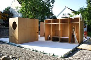 Die Tragstruktur des Gebäudes besteht aus vier begehbaren Holzschränken, welche die auskragenden Dachelemente aus vorgespanntem Beton tragen<br />