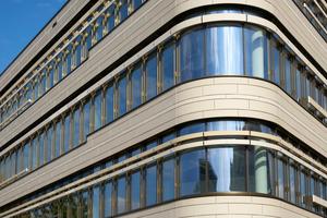 Die hellen, unterschiedlich großen Keramikplatten sind im wilden Verband verlegt und beleben das Fassadenbild durch ihre wahlweise fein horizontal gerillte Linienstruktur oder glatte Oberfläche