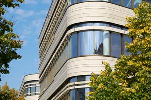 Die horizontal gegliederte Fassade ist von fortlaufenden Fensterbändern und großformatigen Keramikplatten geprägt