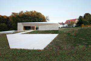 Das Museum wird über die Betonflächen außen zweimal erweitert: hier im Westen in die Obstwiese (für die Museumspädagogik), links nördlich (Café) in Richtung Bestand