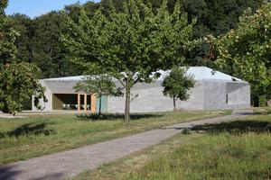 Blick von Westen über die Wiese mit Obstbäumen. Links das große Fenster vor der Pädagogik und zum Teil auch der Ausstellung