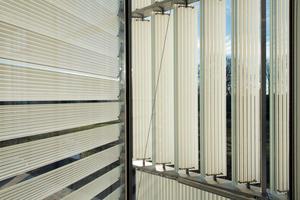 An den Gebäudeecken blickt man von Innen auf vertikale und horizontale Glaslamellen