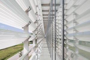 Bewegliche, horizontal verlaufende Lamellen an den Nord- und Südfassaden sind mit weißen Emaillestreifen bedruckt, um das Sonnenlicht abzuhalten