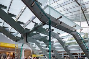 Auch die asymmetrische Eingangs-treppe wurde von Octatube speziell für dieses Projekt entwickelt: Die Trittstufen bestehen aus drei laminierten Glasscheiben, in die an der Rückseite ein Lichtband verarbeitet wurde. Die Haupttragfunktion und Aussteifung übernehmen die gläsernen Geländer zusammen mit den bogenförmigen Glaswänden unterhalb des Zwischenpodests und im Verband mit den Stahlwangen. In letzteren konnten auch die Kabel für die Beleuchtungsinstallationen unsichtbar verlegt werden