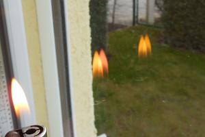 Bild2: Die Position der Wärmeschutzbeschichtung kann bei einigen Isolierverglasungen anhand der andersfarbig reflektierten Flamme erkannt werden