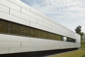 Lediglich ein schmales, langgestrecktes Fensterband durchbricht die silbergraue Stahlblechfassade und sorgt für angenehme Lichtverhältnisse im Innenraum