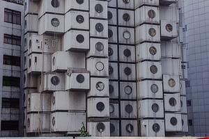 """Capsule Tower, Tokyo, 2018: Ein """"Heimatgefühl"""" im städtischen Kontext ist so ohne Weiteres nicht zu haben. Die Engpässe auf dem Wohnungsmarkt etwa könnten dazu führen, dass nun (wieder) auf eine Art gebaut wird, die Identifikation und Ortsbindung erschwert. Der berühmte Tokioter Kapselturm von Kisho Kurokawa – jener ingeniöse Versuch von 1972, mit vorfabrizierten Wohnzellen eine kurzfristigem Bedarf dienende Wohn- oder eher Schlafmöglichkeit bereitzustellen – ist dafür ein bildhaftes Beispiel. Durchgesetzt hat sich die Idee dankenswerter Weise nicht; heute steht der Tower kurz vor dem Abriss"""