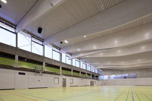 Die dreiteilbare Sporthalle erhält ihr Tageslicht ausschließlich über die nach allen Himmelsrichtungen umlaufenden Fenster. Das verwendete Holz ist generell weiß lasiert mit sichtbarer Maserung
