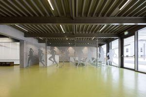 Das Foyer verknüpft die Nutzungen Sporthalle, Mensa und Hallenbad miteinander. Das Trapezblech der Fassade wiederholt sich in Form und Farbe im Innenraum und verknüpt so außen mit innen
