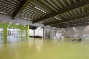 Das neue Foyer mit einem verglasten Aufenthaltsraum öffnet sich mit seiner raumhohen Verglasung und seinem weit auskragenden Vordach zum Vorplatz hin