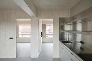 Die Einbauten bestehen aus kieselgrauen Schichtstoffplatten, der Boden aus hellgrauem Linoleum, dazu eine Teeküche mit Edelstahloberflächen. Für die Wohnfläche in Minimalstgröße planten die Architekten die komplette Ausstattung<br />