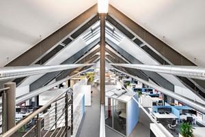 Verschiedene Angebote zum Arbeiten und zum Austausch verbinden sich zu einer lebendigen Bürolandschaft