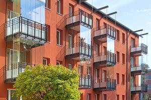 Die rote Farbigkeit der Außenfassade zur Straße bezieht sich auf die historischen Backsteinbauten in der Nachbarschaft. Außerdem ergänzen Wintergärten den Wohnraum