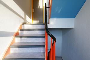 Die sanierten Treppenhäuser sind teils mit kräftigen Farben, wie hier die Decken, in einem leuchtenden Blau, gestaltet