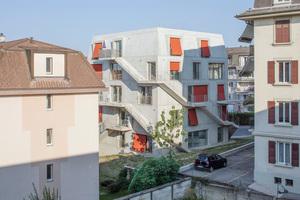 Die roten Markisen sowie das Mansarddach passen zu den Bürgerhäusern des 19. Jahrhunderts, damit hören die Gemeinsamkeiten aber auch schon auf. Um Fläche innerhalb der Gebäudehülle zu sparen, verlegten die Architekten die drei Erschließungstreppen, die gleichzeitig als Fluchtwege im Brandfall dienen, an die Außenfassade