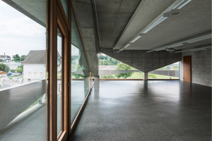 Die Fassaden entstehen aus der Tragstruktur des Betons. Während die Geschossdecken ein lineares Auflager benötigen, reicht für den Lastabtrag ein Pfeiler aus. Daraus resultieren die schrägen Betonkonsolen, die die Innenräume prägen
