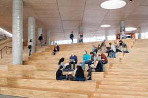 Die großen Treppen im Foyer sind, wie der Großteil der Böden im Sockelbereich, mit Eichenparkett belegt. Zusammen mit den abgehängten Holzlamellendecken sorgt dies für eine angenehme, fast wohnliche Atmosphäre