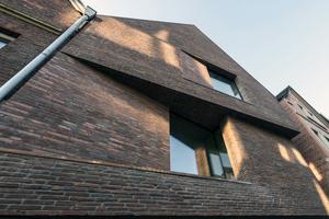 Die Fensteröffnung zum Wohnraum im 1. Obergeschoss gleicht einem skulpturalen Eingriff in die Giebelwand, hier akzentuiert durch einen verglasten Rücksprung, der von einem seitlichen Podest aus den Blick bis zum mittelalterlichen Buddenturm erlaubt