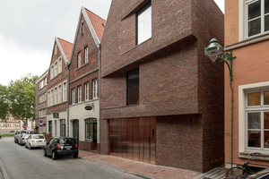 Die strenge, eher verschlossene Straßenansicht wird durch zwei Versprünge in der mit rotbraunem Klinker verkleideten Fassade gestaffelt