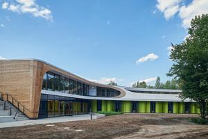 Dynamische Formen und Farben beherrschen den Neubau.Die durchgehende Dachabdichtung mit weißen Dachbahnen schafft eine optische Verbindung zwischen den Ebenen